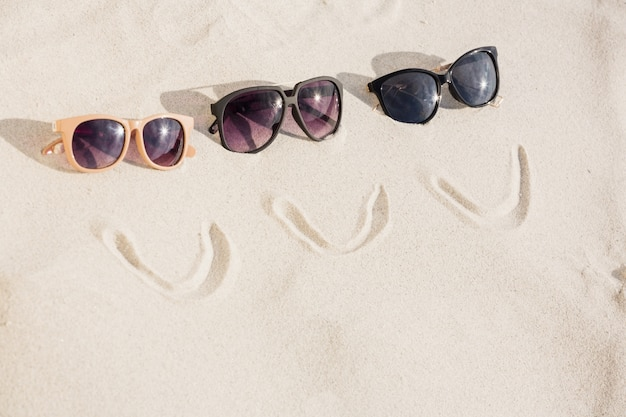 Smiley gesicht und drei sonnenbrillen auf sand