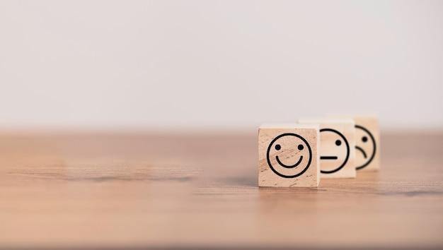 Smiley-gesicht vor normalem und traurigem gesicht, das bildschirm auf holzwürfelblock druckt