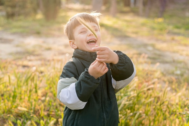 Smiley-junge, der im park spielt
