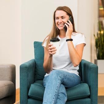 Smiley junge frau, die am telefon spricht