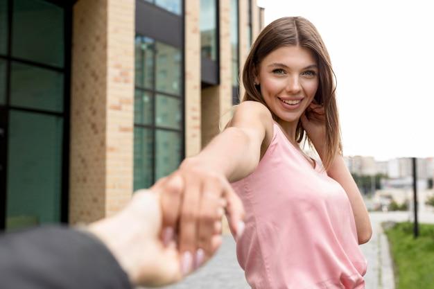 Smiley junge frau, die hände mit ihrem freund hält