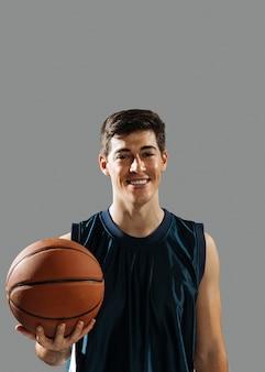 Smiley junger mann, der seinen basketball hält