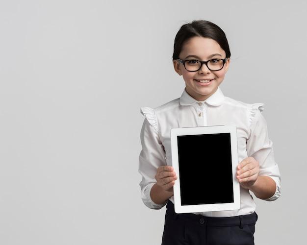Smiley junges mädchen, das tablette mit kopienraum hält