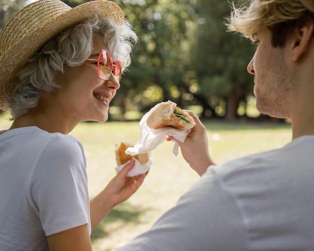 Smiley junges paar, das burger zusammen im park isst
