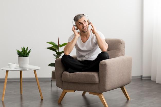 Smiley kerl sitzt auf einem stuhl und hört musik