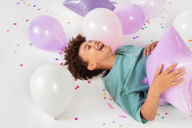 Smiley-kind mit mittlerem schuss, das mit luftballons spielt