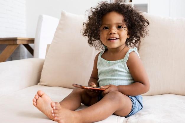 Smiley-kind sitzt im wohnzimmer