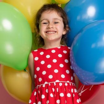 Smiley kleines mädchen in einem roten kleid, das ihren geburtstag feiert