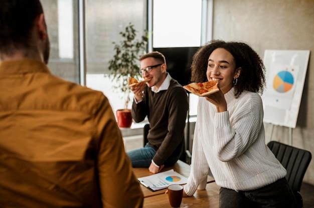Smiley-kollegen, die während einer bürobesprechungspause pizza essen