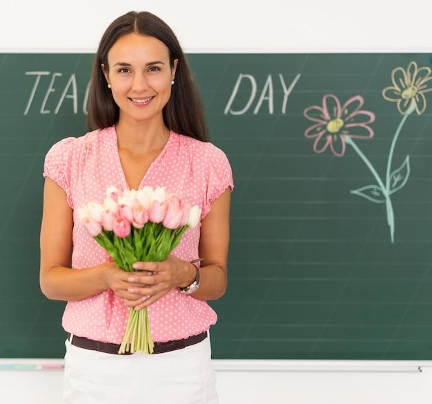Smiley-lehrer, der einen blumenstrauß hält