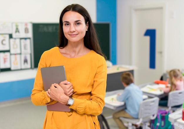 Smiley-lehrer, der im klassenzimmer steht