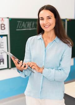 Smiley-lehrer hält eine tablette