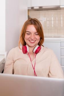 Smiley-lehrer mit kopfhörern, die eine online-klasse von zu hause halten