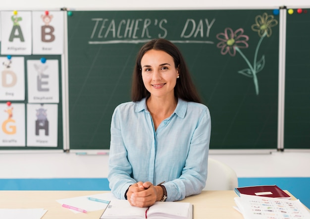 Smiley-lehrerin an ihrem schreibtisch im klassenzimmer