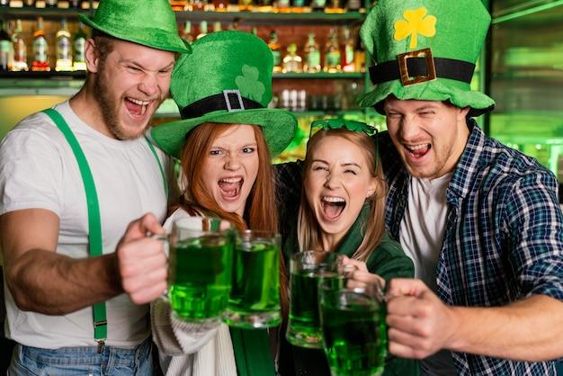 Smiley-leute feiern st. patricks tag an der bar