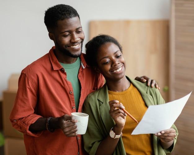 Smiley liebendes paar, das plant, nach hause zu renovieren