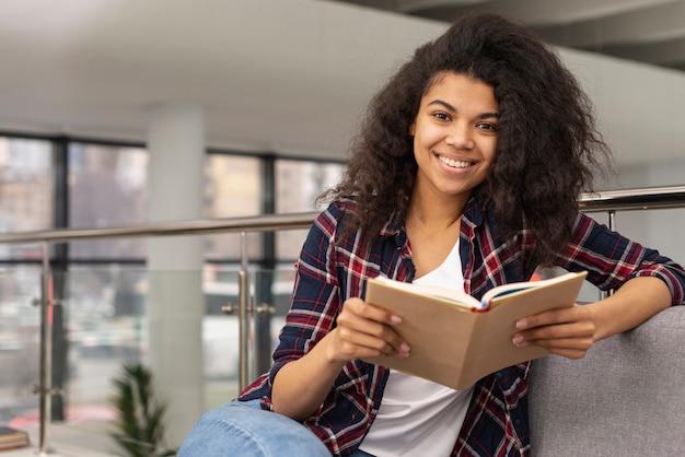 Smiley-mädchen auf der couch beim lesen