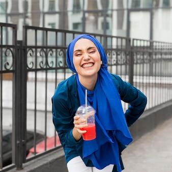 Smiley-mädchen, das einen hijab trägt und einen smoothie hält