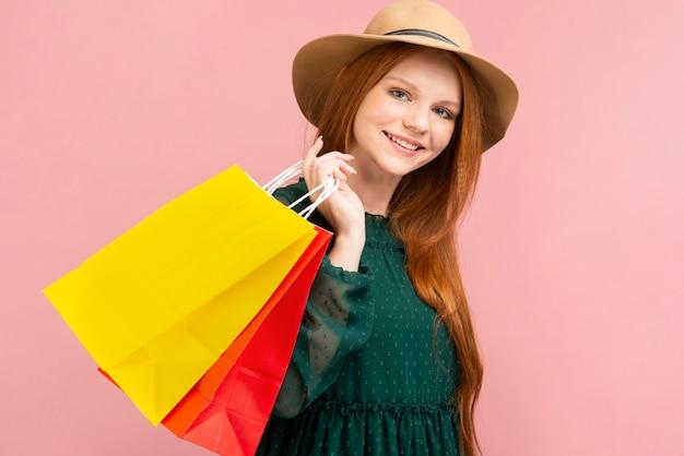 Smiley-mädchen, das einkaufstaschen hält