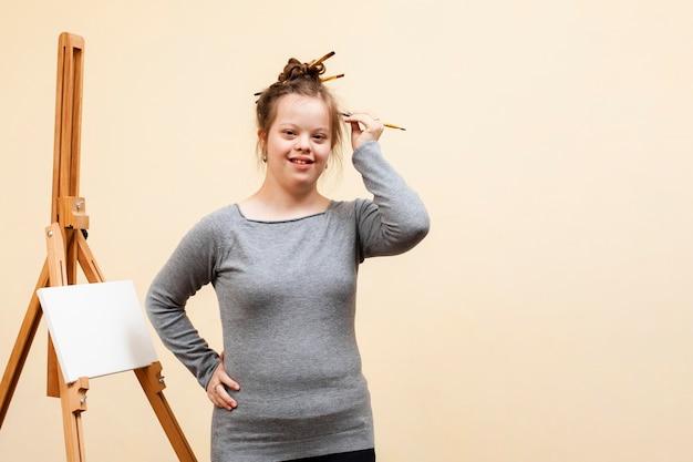 Smiley-mädchen mit down-syndrom posiert beim halten des pinsels