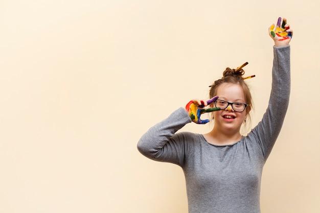 Smiley-mädchen mit down-syndrom und bunten handflächen