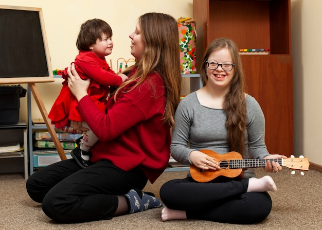 Smiley-mädchen mit down-syndrom und frau, die kind hält