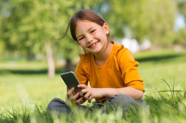 Smiley-mädchen mit mittlerem schuss, das smartphone hält