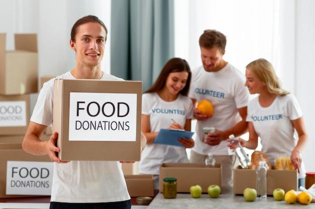 Smiley männlicher freiwilliger, der box mit bestimmungen für welternährungstag hält
