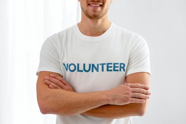 Smiley männlicher freiwilliger, der mit verschränkten armen aufwirft
