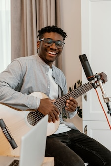 Smiley männlicher musiker zu hause, der gitarre spielt und singt