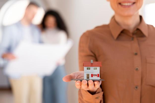 Smiley-maklerin, die miniaturhaus mit paar hält, das pläne im hintergrund betrachtet