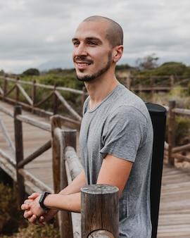 Smiley-mann am strand, der die aussicht bewundert, bevor er yoga macht
