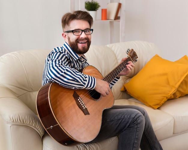 Smiley-mann auf dem sofa, das gitarre spielt