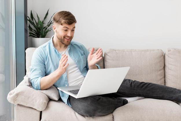 Smiley-mann auf der couch mit laptop
