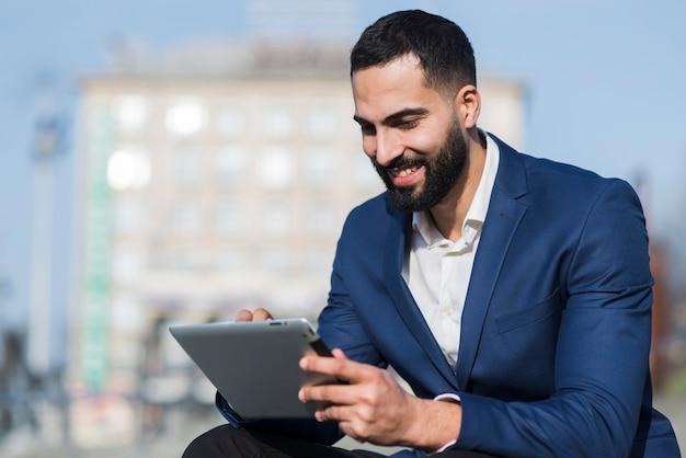 Smiley-mann, der an tablette arbeitet