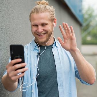 Smiley-mann, der auf smartphone spricht