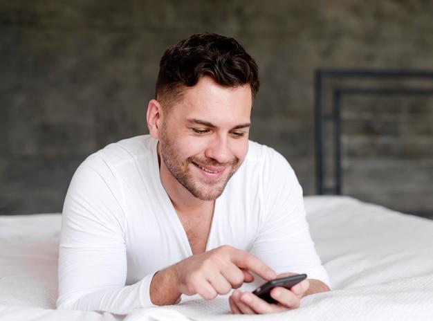Smiley-mann, der auf smartphone tippt
