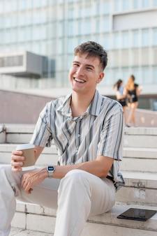 Smiley-mann, der auf stufen draußen sitzt, während tasse kaffee hält