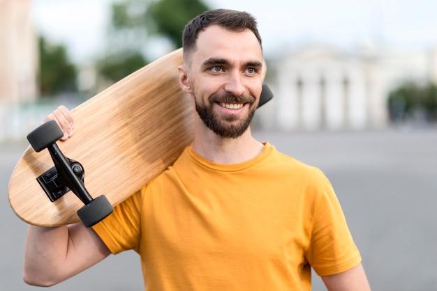 Smiley-mann, der ein skateboard hält