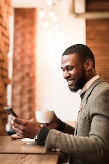 Smiley-mann, der eine tasse mit kaffee in einer kneipe hält