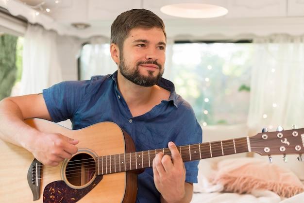 Smiley-mann, der in seinem wohnwagen gitarre spielt