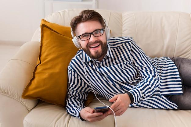 Smiley-mann, der musik auf kopfhörern genießt
