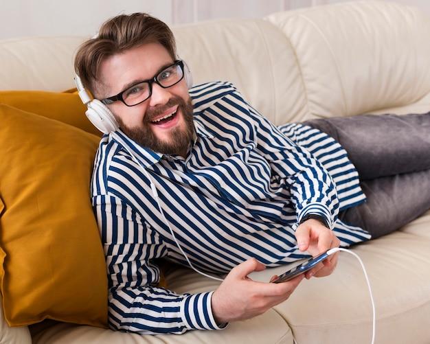 Smiley-mann, der musik auf kopfhörern hört