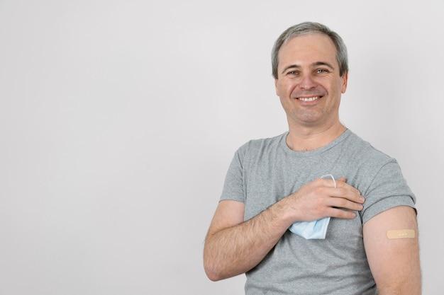 Smiley-mann, der nach der impfung einen verband am arm zeigt