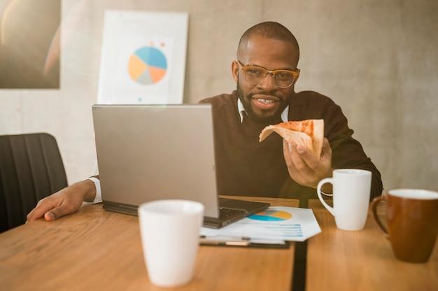 Smiley-mann, der pizza während einer bürobesprechungspause hat