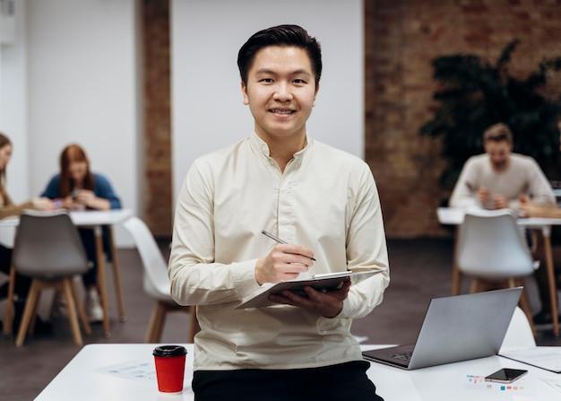 Smiley-mann, der projektdokumente im büro hält