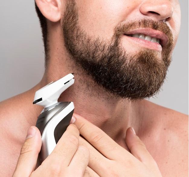 Smiley-mann, der seinen bart rasiert