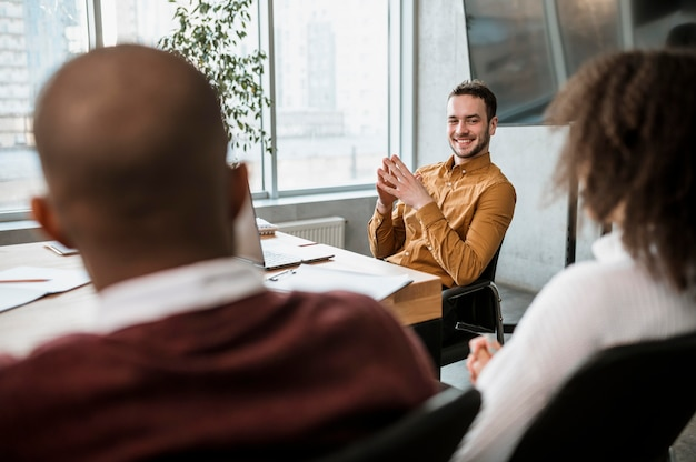 Smiley-mann, der während eines treffens mit seinen kollegen spricht