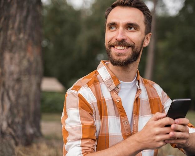 Smiley-mann im freien, der smartphone hält