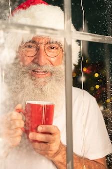 Smiley-mann im weihnachtsmannhut, der becher hält und durch fenster schaut